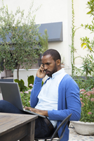 Man making phone call while using laptop computer outdoors 11025008044  写真素材・ストックフォト・画像・イラスト素材 アマナイメージズ