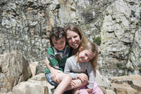 Mother and children sitting on rock formation, portrait