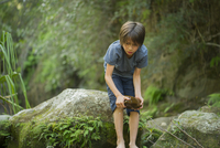 Boy bending over to pick up large wet rock