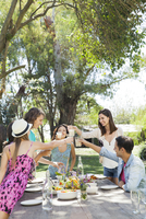 Friends having meal together outdoors, clinking glasses 11025008923| 写真素材・ストックフォト・画像・イラスト素材|アマナイメージズ