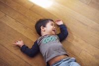 Little boy lying on floor laughing