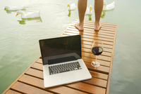 Man standing on lake dock, laptop computer and wine glass in foreground