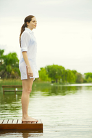 Woman standing at end of lake dock looking at view