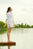 Woman standing at edge of lake dock with eyes closed