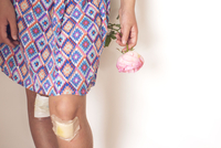 Girl with bandaged knees holding rose, cropped