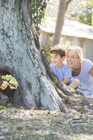 Young boy and mother hiding behind tree, playing hide-and-seek 11025009749| 写真素材・ストックフォト・画像・イラスト素材|アマナイメージズ