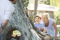 Young boy and mother hiding behind tree, playing hide-and-seek