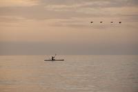 Person kayaking at sunset
