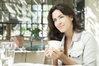 Young woman enjoying cup of coffee outdoors 11025010038| 写真素材・ストックフォト・画像・イラスト素材|アマナイメージズ