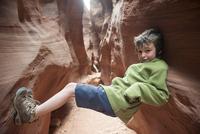 Boy balancing in narrow slot canyon 11025010341| 写真素材・ストックフォト・画像・イラスト素材|アマナイメージズ