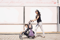Mother pushing toddler son in stroller on sidewalk 11025010451| 写真素材・ストックフォト・画像・イラスト素材|アマナイメージズ