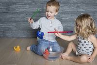 Children using toy fishing rods to catch rubber ducks floating in large bowl