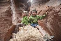 Children sitting on rock formation in Utah, USA 11025010530| 写真素材・ストックフォト・画像・イラスト素材|アマナイメージズ