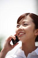 携帯電話で話す20代のオフィスレディ