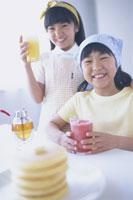ホットケーキとジュースを飲む姉妹 11026001169| 写真素材・ストックフォト・画像・イラスト素材|アマナイメージズ