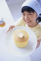 ホットケーキの皿を持つ女の子