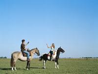 Young man and woman riding horses 11027003154| 写真素材・ストックフォト・画像・イラスト素材|アマナイメージズ