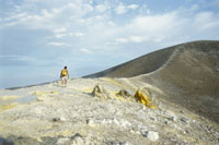 hiker on rim of volcano crater
