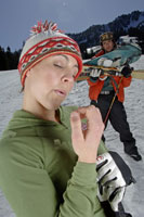 Woman relaxing while friend carries skis 11029000183| 写真素材・ストックフォト・画像・イラスト素材|アマナイメージズ