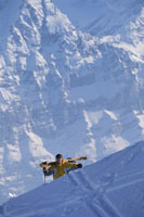 Skier climbing mountain carrying skis