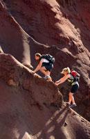 Young women climbing cliff wall, Hawaii