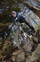 Boy riding mountain bike on rocks