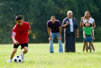 boy kicks soccer ball as family watches