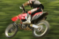 Blurred motorcyclist jumping midair