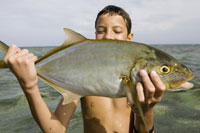 Boy standing in ocean holding fish