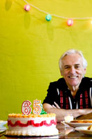 Senior man celebrating his 65th birthday 11029000840| 写真素材・ストックフォト・画像・イラスト素材|アマナイメージズ