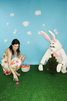 Woman and Easter bunny collecting eggs
