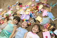 Young girls laying in mess of toys