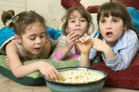 girls eating popcorn at a sleepover
