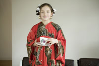 Young girl in kimono serving tea