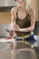 Glamorous woman cutting meat with knife