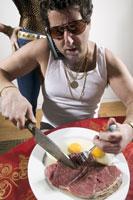 Man eating raw steak and eggs 11029001027| 写真素材・ストックフォト・画像・イラスト素材|アマナイメージズ