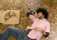 man asleep after pizza and beer feast