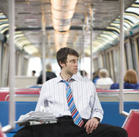 Businessman with newspapers on a train 11029001082| 写真素材・ストックフォト・画像・イラスト素材|アマナイメージズ