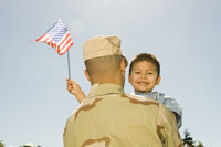 Hispanic military soldier holding son