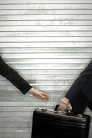woman handing off suitcase to partner