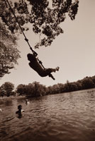 Boy swinging into lake