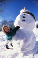 Girl posing with snowman