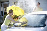 Young couple playing and washing car