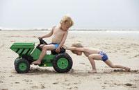 Boys playing with toy digger on beach 11029002194| 写真素材・ストックフォト・画像・イラスト素材|アマナイメージズ