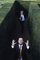Man chasing another in hedge maze
