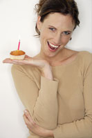 Woman holding birthday cake with candle