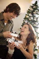 Couple exchanging Christmas gifts 11029002420| 写真素材・ストックフォト・画像・イラスト素材|アマナイメージズ