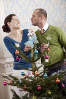 Couple decorating a Christmas tree 11029002427| 写真素材・ストックフォト・画像・イラスト素材|アマナイメージズ