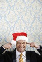 Man in Santa hat putting fingers in ears