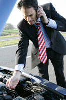 Businessman having car trouble